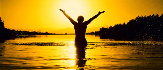 Achieving happiness through positive action. A person standing in the sunset with arms lifted in victory. A Flourishing Life Society Article header