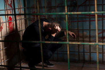 Man locked in cage. Representing the imprisonment of self-sabotaging behaviors.